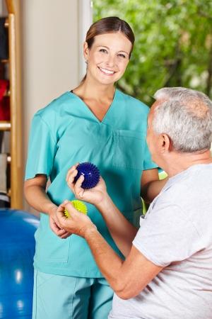 terapia ocupacional: Fisioterapeuta hombre mayor que muestra un ejercicio con una pelota spikey Foto de archivo