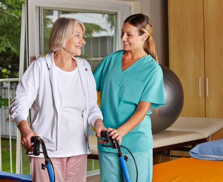 fysiotherapie: Fysiotherapeut helpt senior vrouw met rollator op heilgymnastiek Stockfoto