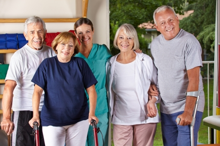 occupational therapy: Group of happy senior people in gym with physiotherapist
