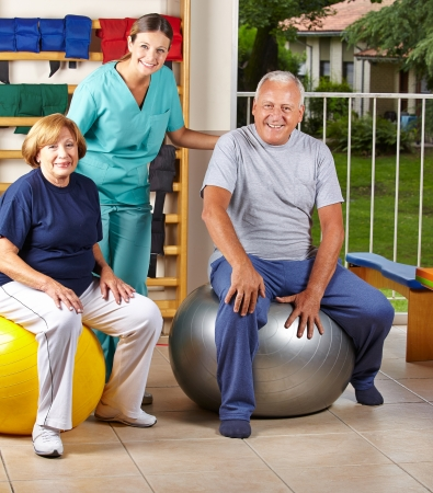physiotherapist: Two senior people sitting on gym ball in physiotherapy