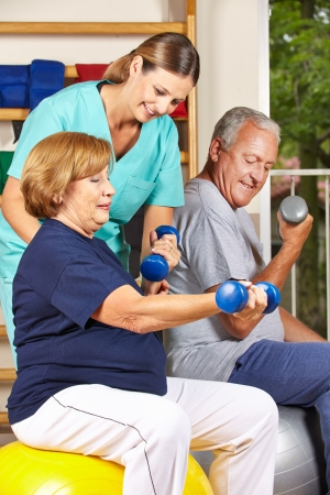 therapy group: Two senior people doing dumbbell fitness training with physiotherapist