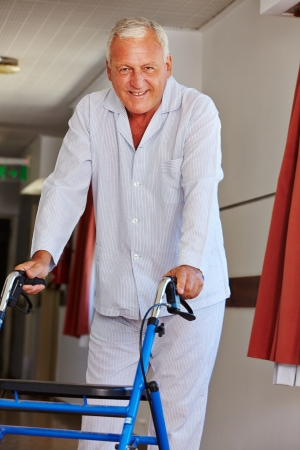 Senior man walking with a walker throough the floors of a nursing home photo