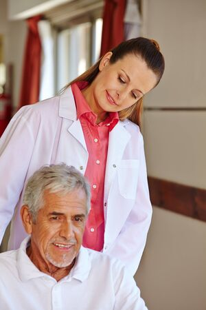 care allowance: Nurse with senior patient in a wheelchair in a hospital