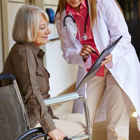 Nurse in a hospital asking a senior woman in wheelchair for signature photo