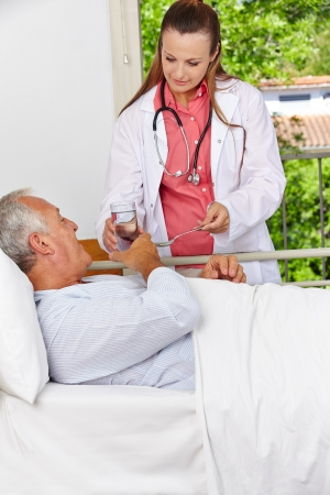 nursing allowance: Senior in hospital taking medicine with a glass of water Stock Photo