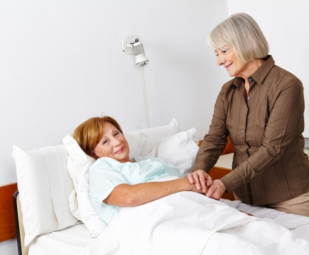 Old sick woman getting a senior visitor in the hospital photo