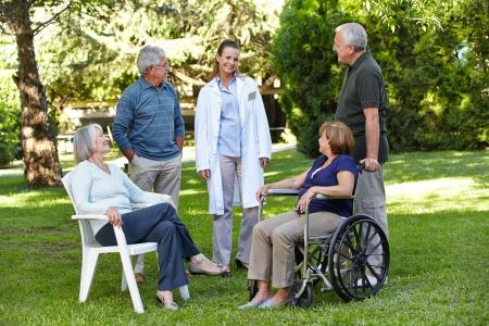 Geriatrische verpleegster met senior groep in de tuin van een bejaardentehuis Stockfoto