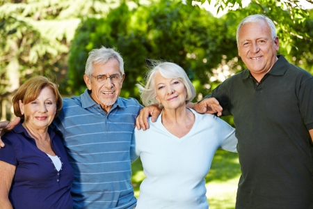 pensioner: Four happy semiling senior people standing in nature in summer Stock Photo