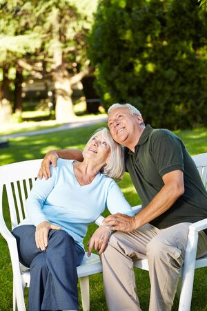 Old senior couple sitting in their garden and looking up Stock Photo - 17825190