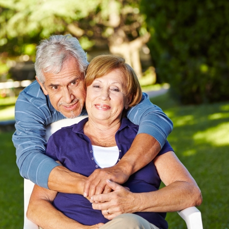 elderly couples: Happy senior couple in love in fall outside in a garden Stock Photo