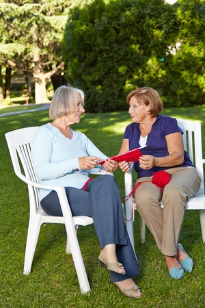 Two senior women knitting a scarf together in a summer garden photo