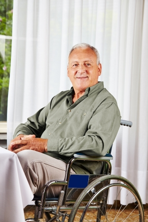 care allowance: Smiling senior sitting in a wheelchair in a nursing home Stock Photo