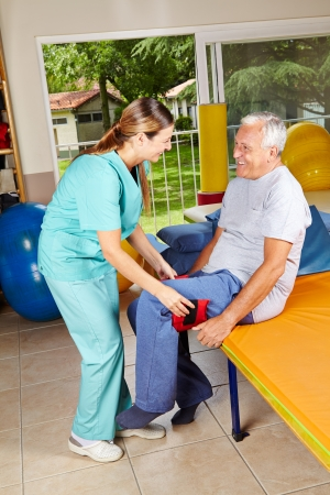 nursing service: Elderly man moving his legs at physiotherapy with the help of physiotherapist Stock Photo