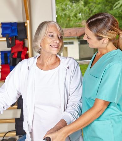 terapia ocupacional: Mujer mayor en gimnasia correctiva mirando fisioterapeuta
