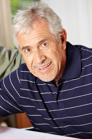 nursing allowance: Portrait of a happy smiling elderly man in a retirement home Stock Photo