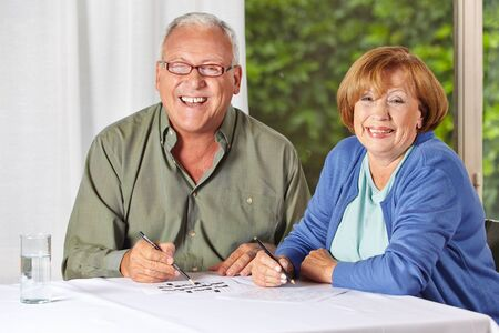 Two happy senior people solving riddles in a retirement home photo