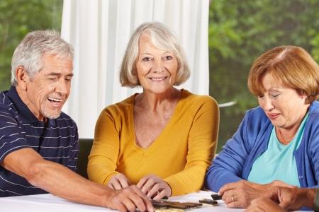 persona mayor: Tres ancianos jugando una partida de dominó en un hogar de ancianos Foto de archivo