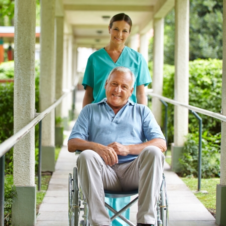 mobility nursing: Happy nurse pushing wheelchair with senior man in hospital garden