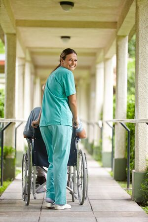 Smiling nurse pushing senior man in wheelchair in a nursing home Stock Photo - 17853873