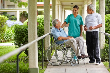 rehab: Two senior citizens talking to a nurse in a hospital garden Stock Photo