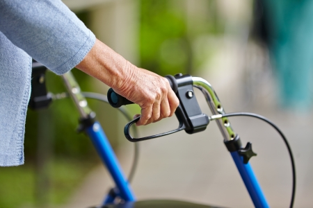 discapacidad: Manos de una mujer mayor en las asas de un andador Foto de archivo
