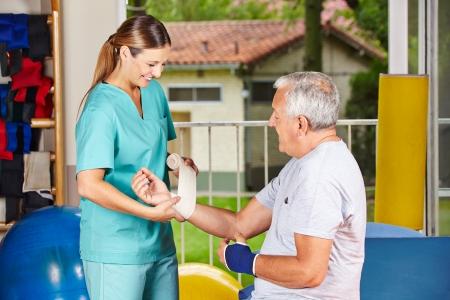 terapia ocupacional: Enfermera cambiar el vendaje en la muñeca del hombre mayor en fisioterapia Foto de archivo