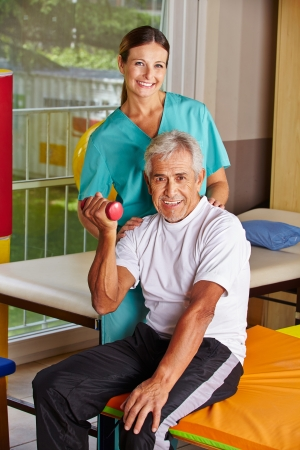 remedial: Senior man lifting dumbbells at remedial gymnastics with physiotherapist Stock Photo