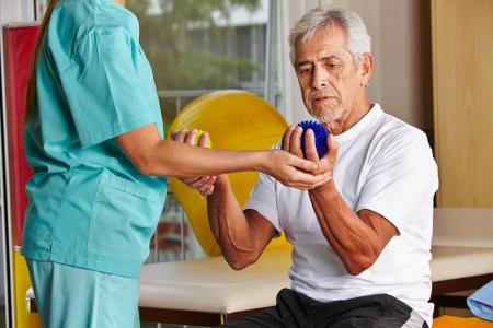 terapia ocupacional: Hombre mayor con las bolas puntiagudas en el gimnasio con el fisioterapeuta Foto de archivo