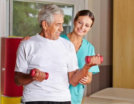 Hombre mayor con mancuernas en rehabilitación con un fisioterapeuta