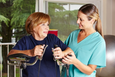 terapia ocupacional: Enfermera ayuda a la mujer mayor en un centro de rehabilitación en fisioterapia