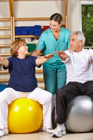 Two senior people doing back fitness training with physiotherapist photo