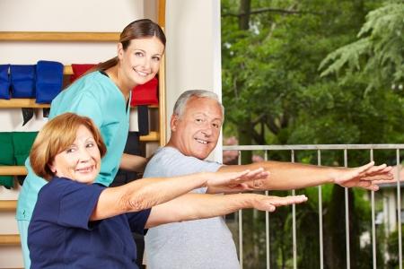 terapia de grupo: Feliz fisioterapeuta con las personas mayores haciendo ejercicios de fitness para la espalda