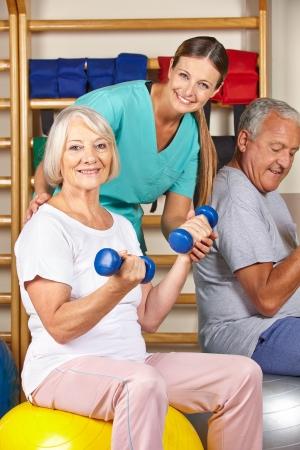terapia ocupacional: Feliz el hombre mayor y una mujer en el gimnasio haciendo fitness en un hogar de ancianos