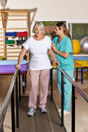 terapia ocupacional: Mujer mayor que sostiene barandilla en fisioterapia con una enfermera Foto de archivo
