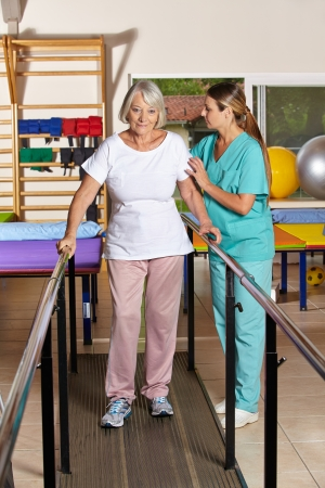 Senior woman holding railing in physiotherapy with a nurse photo