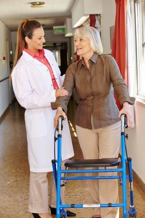 marcheur: Infirmi�re de parler au patient a�n� avec d�ambulateur � l'h�pital Banque d'images