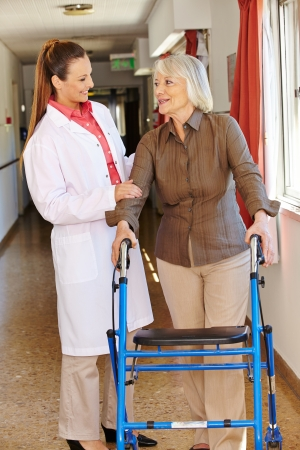 human kind: Nurse talking to senior patient with walker in hospital Stock Photo