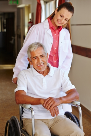 mobility nursing: Senior man in wheelchair with nurse in a hospital