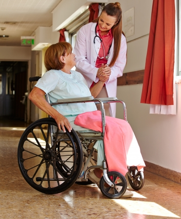 paralyzed: Nurse holding hand of female senior patient in wheelchair Stock Photo