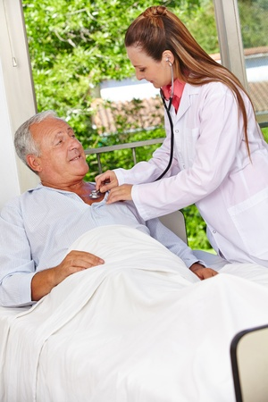 Doctor auscultating patient in hospital bed with stethoscope photo