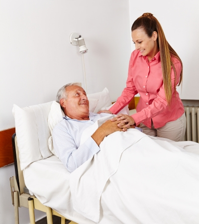 healthcare visitor: Daughter vising her old father at sickbed in hospital Stock Photo