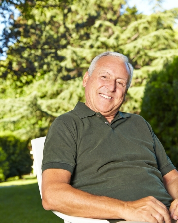 Happy old man sitting in a summer garden photo