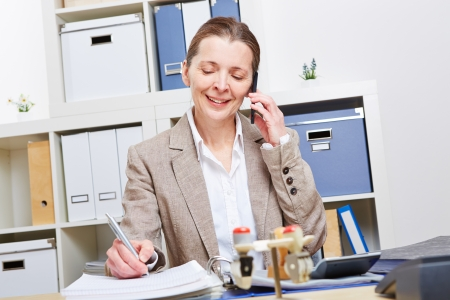 office notes: Elderly woman in business office using smartphone to make a call