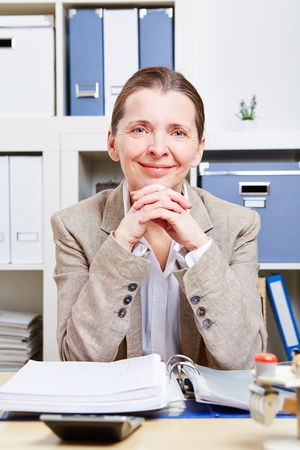 Portrait of happy senior business woman sitting at her desk in the office Stock Photo - 18064440