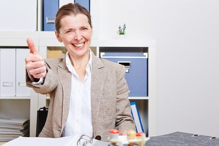 Happy senior business woman in her office holding her thumbs up Stock Photo - 18064497