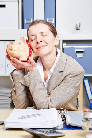 Senior business woman with piggy bank in her office at the desk Stock Photo - 18064441