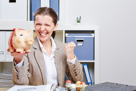 Successful senior business woman with piggy bank cheering in her office Stock Photo - 18064496