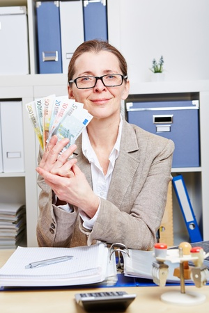 Elderly woman with glasses holding Euro money bills in her office Stock Photo - 18064495