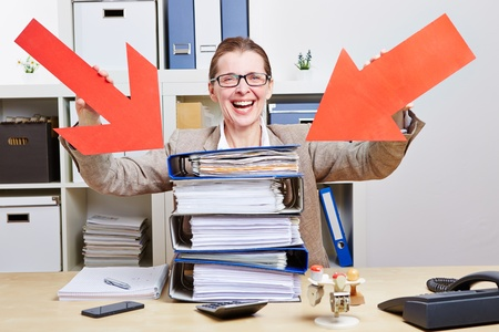 Happy business woman in office pointing arrows to stack of files photo