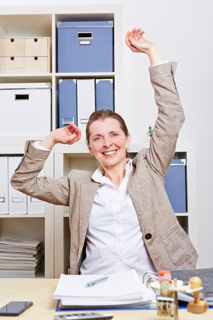 Senior business woman in office stretching her back photo